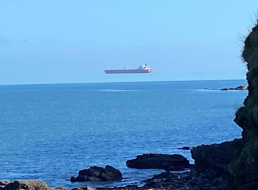 A tanker appears to float above the sea when viewed from the Cornwall coast