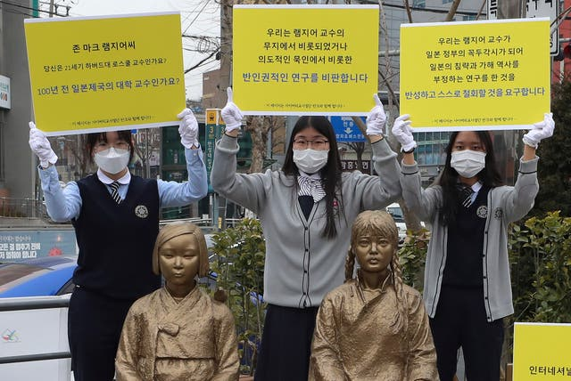 <p>High school students hold up banners to protest a recent academic paper by Harvard University professor J Mark Ramseyer, behind statues symbolising wartime sex slaves in Seoul, South Korea</p>