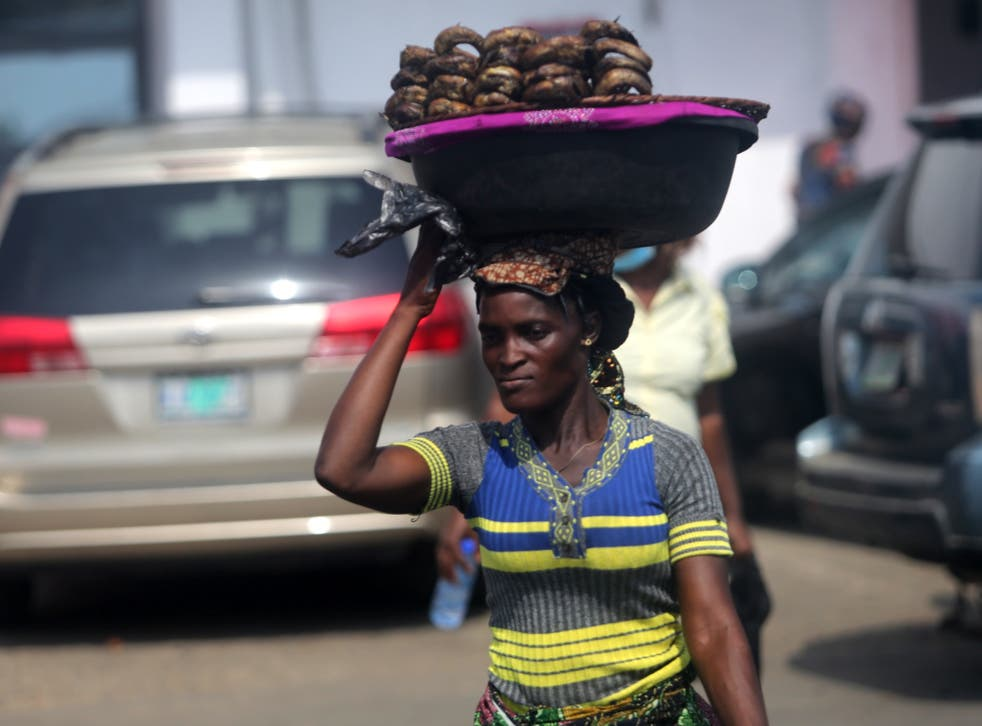 A woman hawks smoked fish displayed on a plastic bowl along a road in Oyingbo district of Lagos, Nigeria