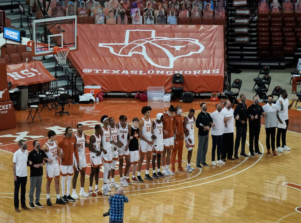 """FILE - In this Sunday, Dec. 20, 2020, file photo, Texas players sing """"The Eyes Of Texas"""" after an NCAA college basketball game against Oklahoma State in Austin, Texas. The University of Texas' long-awaited report on the history of the school song """"The Eyes of Texas� found it had """"no racist intent,� but the school will not require athletes and band members to participate in singing or playing it at games and campus events. The song had erupted in controversy in 2020 after some members of the football team demanded the school stop playing it because of racist elements in the song's past. (AP Photo/Chuck Burton, File)"""