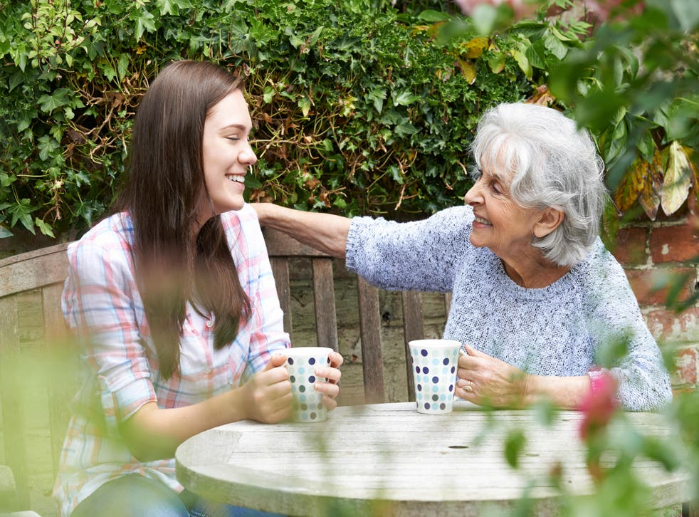 Grandmother and granddaughter chatting over tea