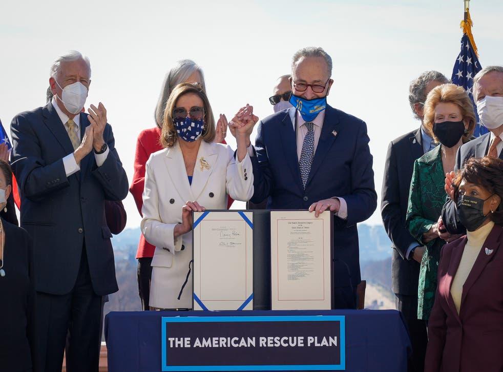 <p>Nancy Pelosi and Chuck Schumer sign the $1.9 trillion Covid-19 relief bill</p>