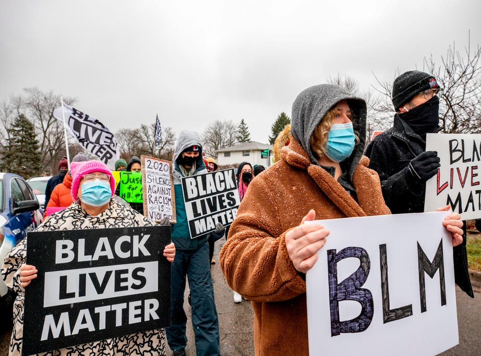 <p>Shawn Finley, a resident and protest organizer, holds a BLM sign as she marches along with protesters in a demonstration against the police killing of Andre Hill in the neighborhood where Hill was shot, in Columbus, Ohio on December 24, 2020. (Photo by STEPHEN ZENNER / AFP) </p>