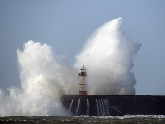 Waves crash over the harbour wall in Newhaven, southern England