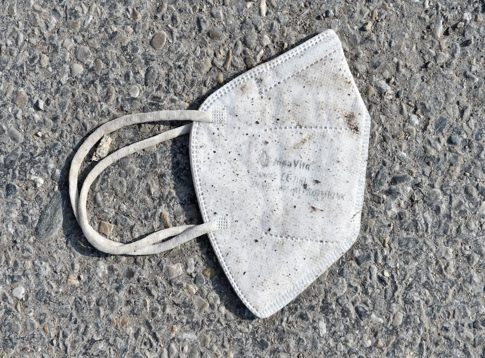 A discarded FFP2 protective face mask lies on a street.