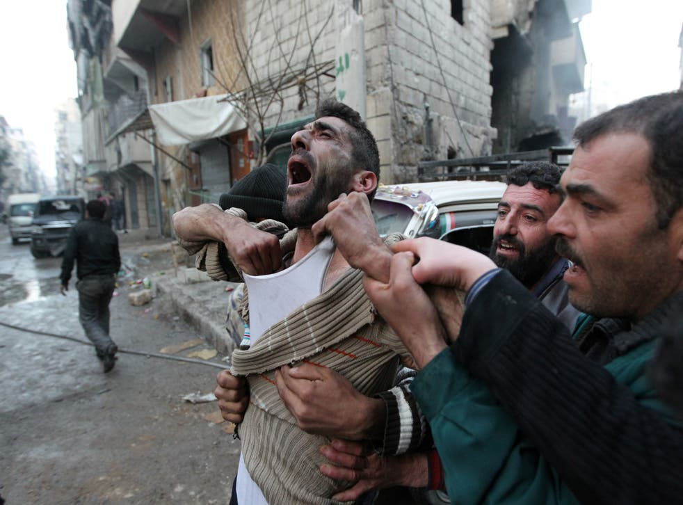 <p>A father reacts after the death of two of his children, whom activists said were killed by shelling by forces loyal to Syria's president Bashar al-Assad, at al-Ansari area in Aleppo, Syria in January 2013</p>