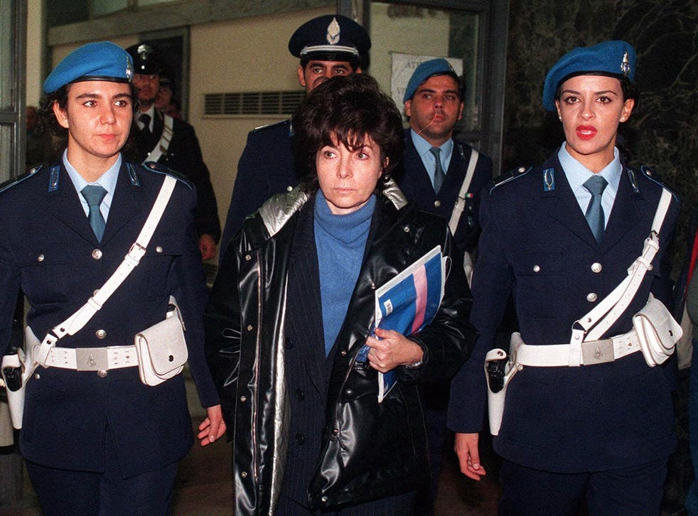Patrizia Reggiani is escorted by police officers into Milan's court on 3 November 1998