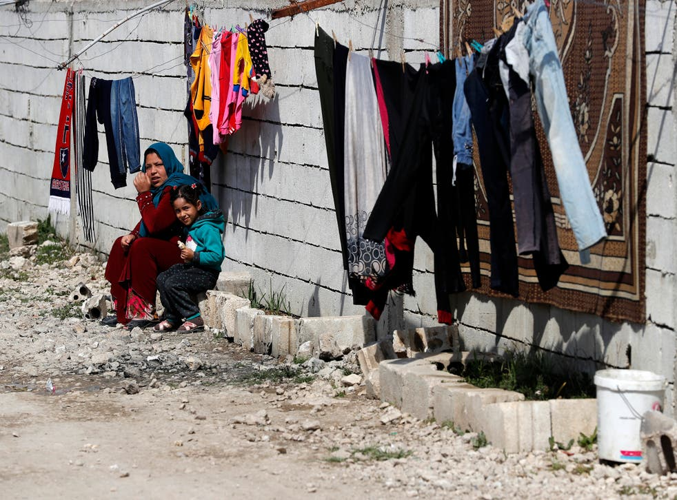<p>A displaced Syrian woman with her daughter at a refugee camp in Bar Elias, in eastern Lebanon's Bekaa Valley</p>