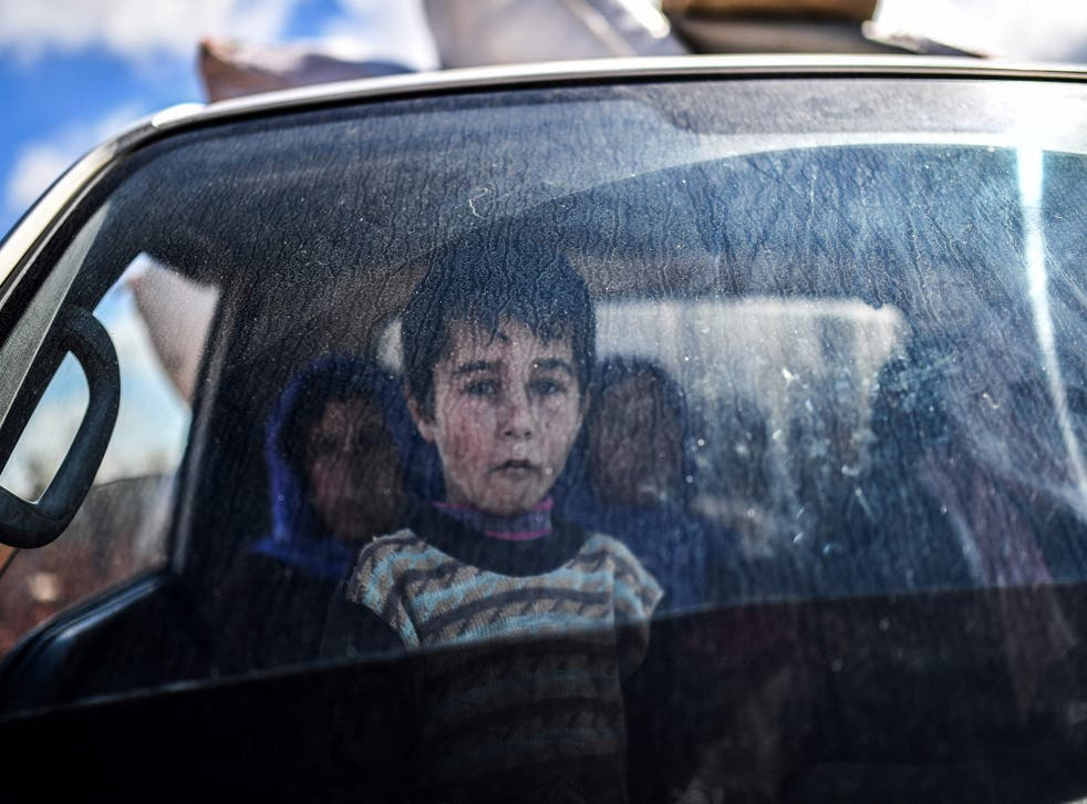 <p>A Syrian child looks on as people arrive at a checkpoint in the village of Anab, northern Syria,</p>