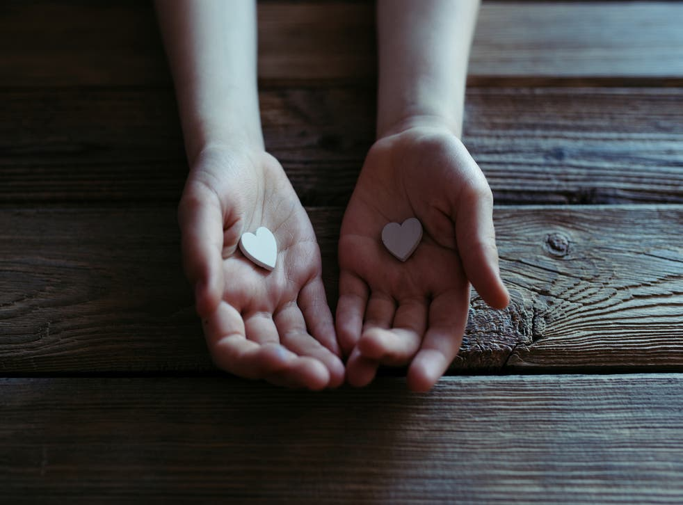 Child holding white hearts in hands over a wooden table.