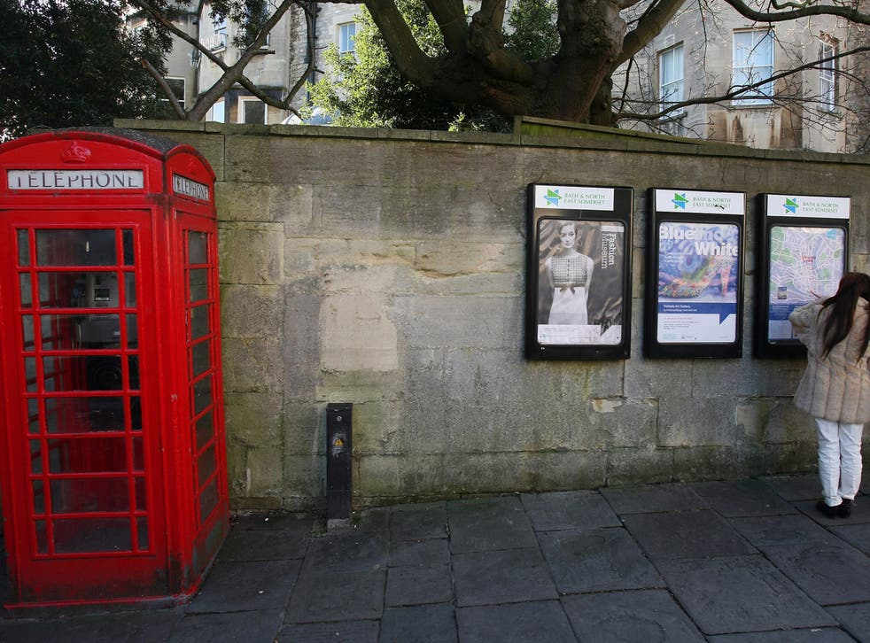 Two women look at posters on a wall beside a traditional red telephone box on a street in Bath