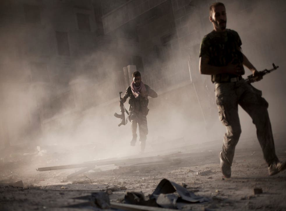 Free Syrian Army fighters run away after attacking a Syrian Army tank during fighting in the Izaa district in Aleppo, Syria