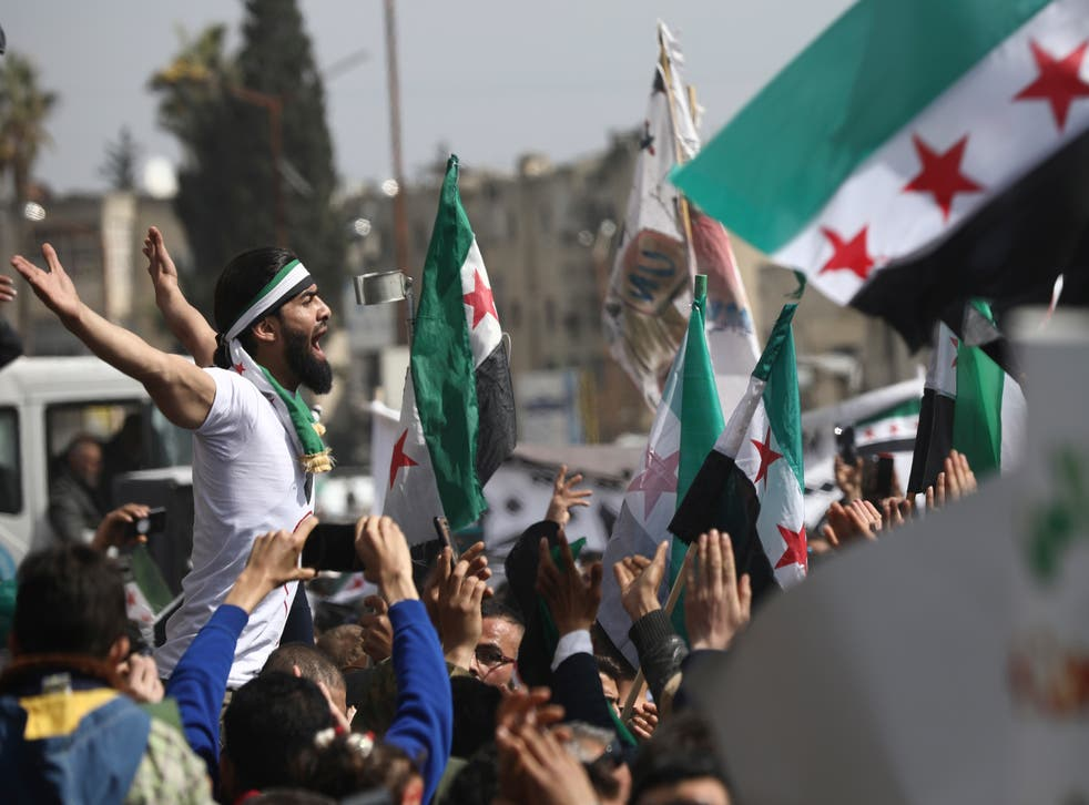 <p>Anti-Syrian government protesters in Idlib mark 10 years since the start of a popular uprising against Assad</p>