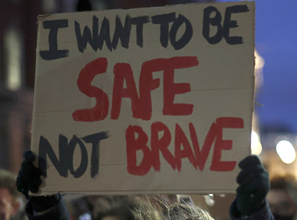 <p>A woman holds up a sign at a protest for women's safety on the streets</p>