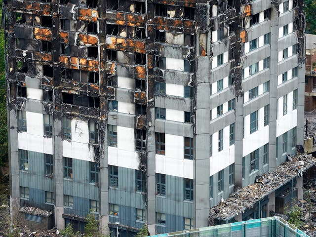 Remains of the tower's unburned lower floors, with untouched cladding still in place, are pictured on 22 June 2017 – eight days after the fire