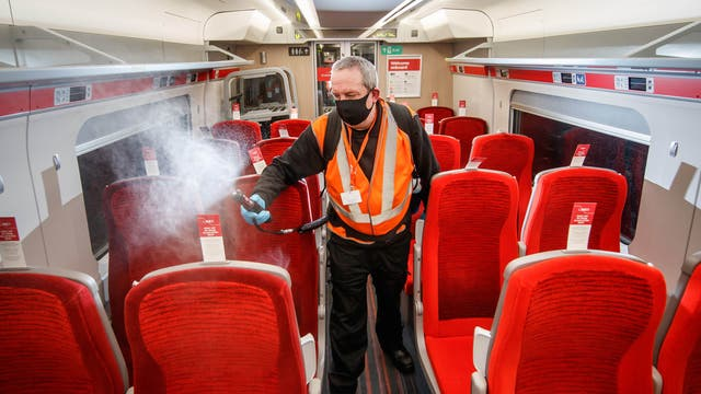 A cleaner uses a fogging machine to clean a train carriage early in the morning