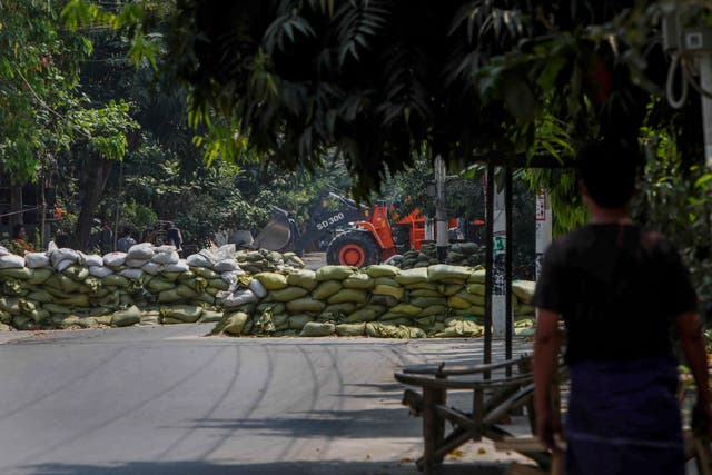 <p>A man watches as soldiers use a bulldozer to remove sandbag barricades put in place by anti-coup protesters in Mandalay, Myanmar</p>