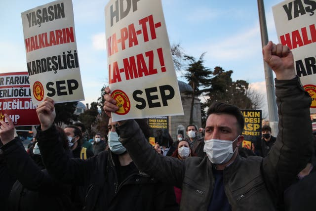 People hold banners and shout slogans during a protest against moves to ban pro-Kurdish HDP in Istanbul