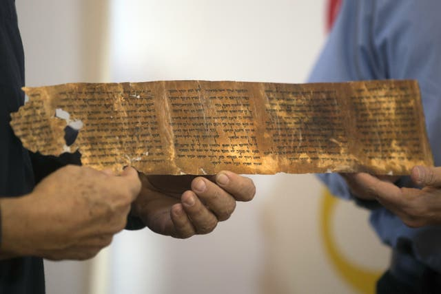 <p>Keep scrolling: Researchers hold a replica of one of the seven ancient biblical manuscripts found in a cave at Qumran near the Dead Sea</p>