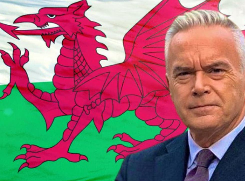 <p>Huw Edwards proudly posed in front of the Welsh national flag</p>