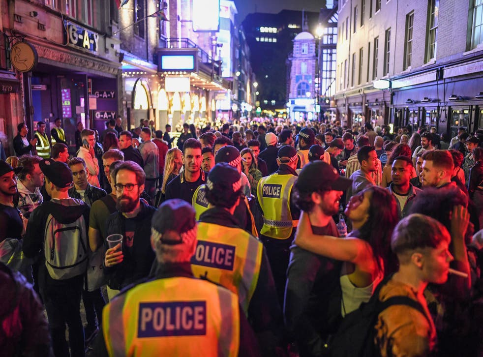<p>Police officers walking through heavy crowds in Soho on 4 July 2020, the day pubs, clubs and restaurants reopened</p>