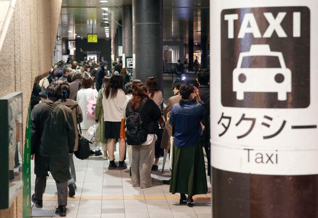 <p>People queue for taxis as train services are suspended following an earthquake in Sendai, Miyagi prefecture on Saturday</p>