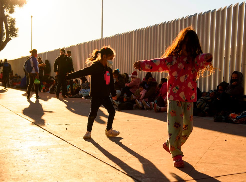 <p>Children play as families of asylum seekers wait outside the El Chaparral border crossing port as they wait to cross into the United States in Tijuana, Baja California state, Mexico </p>