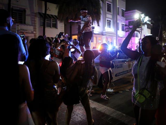 <p>Un hombre baila encima de un coche de policía mientras los juerguistas disfrutan de las festividades de las vacaciones de primavera a pesar del toque de queda a las 8 p.m. impuesto por las autoridades locales, en medio de la pandemia de la enfermedad del coronavirus (COVID-19), en Miami Beach, Florida, EE. UU., 20 de marzo de 2021. </p>