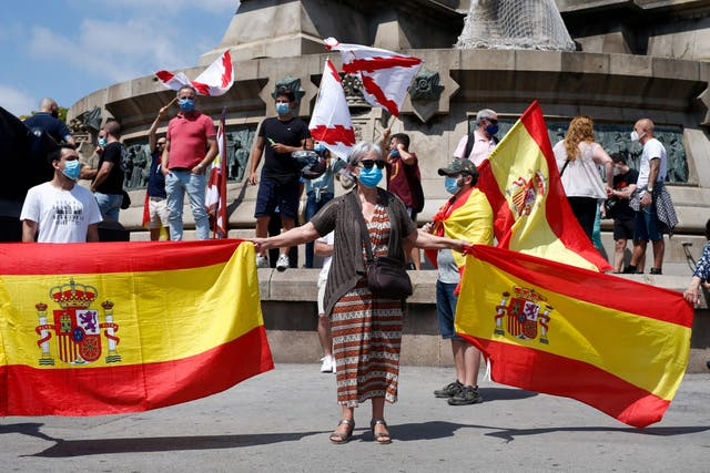 <p>Protesters hold Spanish national flags and Cross of Burgundy flags during a demonstration by Spain's far-Right Vox party to preserve a statue of Christopher Columbus</p>