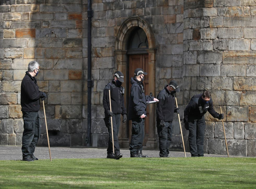 Police officers search within the grounds of the Palace of Holyroodhouse in Edinburgh after a bomb disposal team was called to a 'suspicious item' at the Queen's residence
