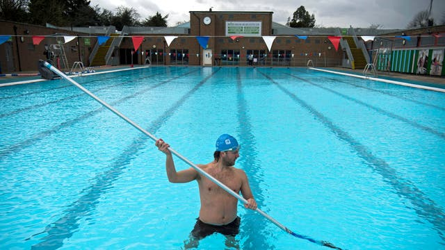 A member of staff, in the pool, cleans the bottom of the pool during pre-opening preparation and cleaning of Charlton Lido, south London, following its closure due to lockdown