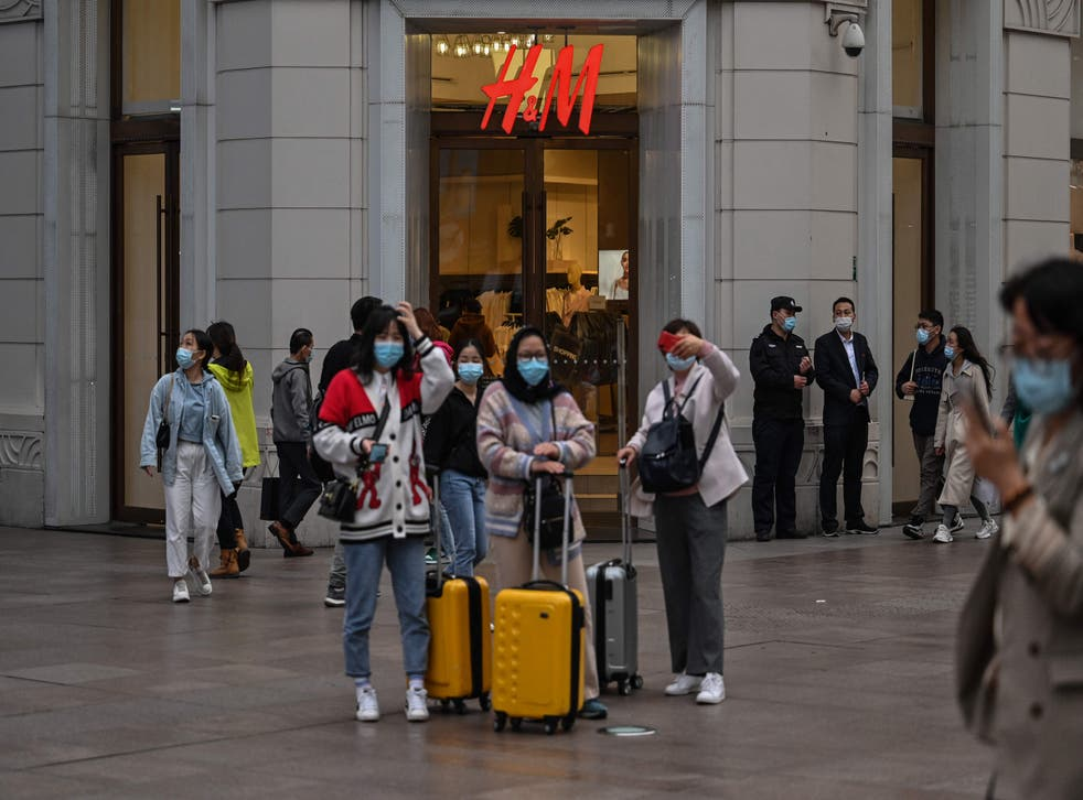 <p>People walk past a store of Swedish clothing giant H&M in Shanghai on 26 March 2021</p>