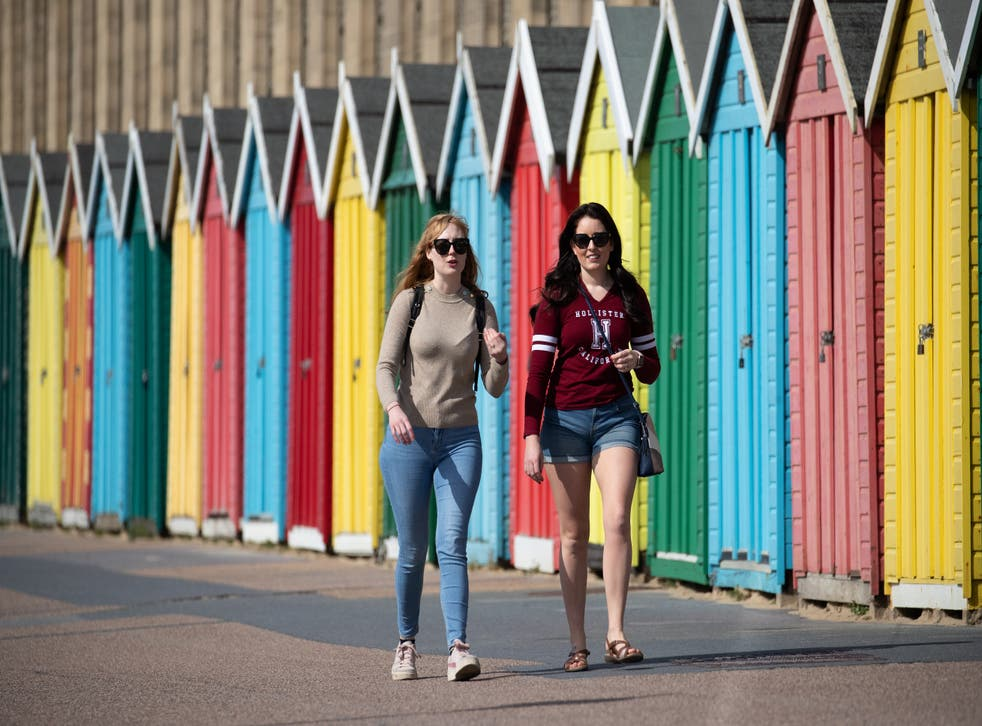 People make their way past beach huts on the sea front on Boscombe beach in Dorset