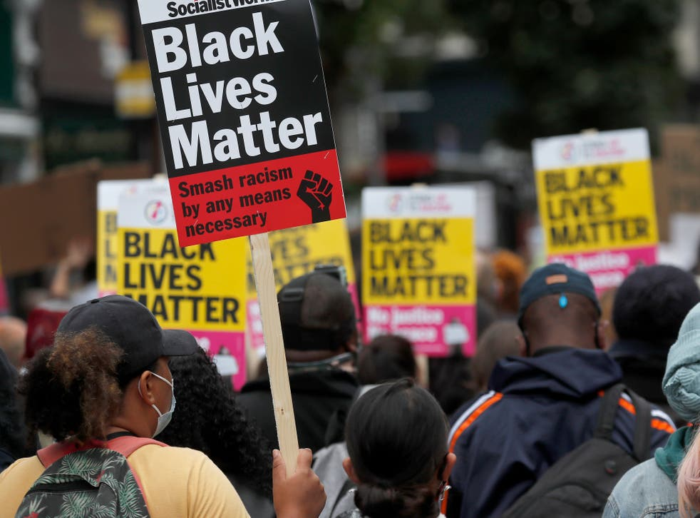 <p>Black Lives Matter protesters hold posters as they march through London's Notting Hill in August 2020</p>