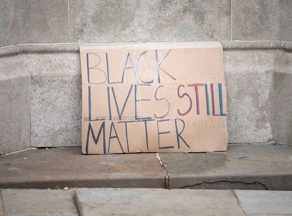 <p>BLM placard placed on the plinth of an Edward Colston statue in Bristol</p>