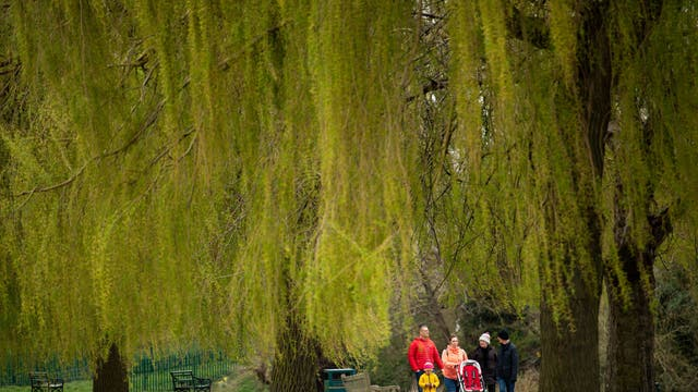 A family walks in St Nicholas' Park in Warwick, the hot weather which baked much of the UK this week is set to give way to a chilly Easter weekend.