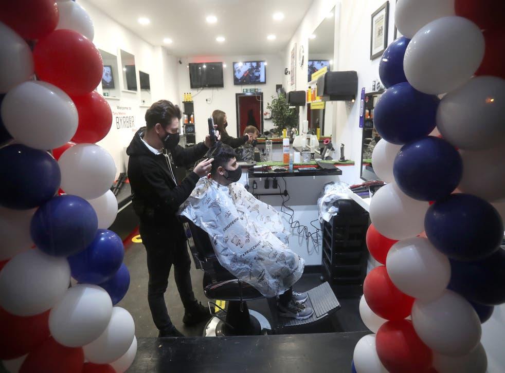 Barber Tony Mann trims Maxx Mann's hair at Tony Mann's Barber Shop in Giffnock near Glasgow
