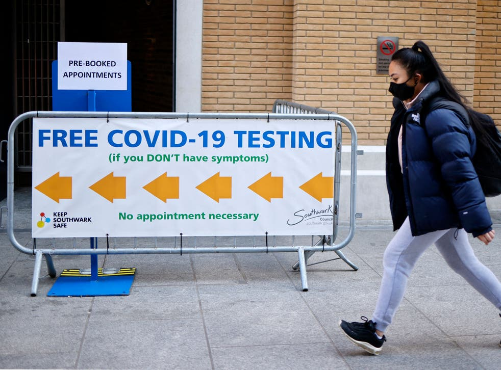A pedestrian wearing a face covering walks past a sign directing people to a rapid lateral flow Covid-19 testing centre at London Bridge train station
