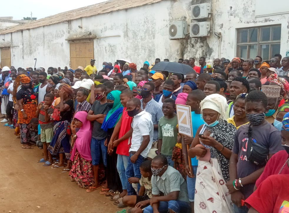 People wait for friends and relatives as a ship carrying more than 1,000 people fleeing an attack claimed by Isis-linked insurgents on the town of Palma, docks in Pemba, Mozambique