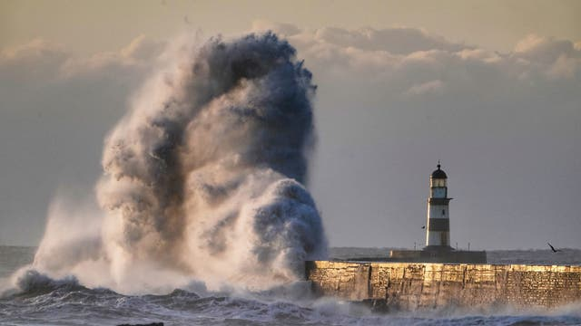 Waves crash over the walls next to Seaham Lighthouse in Durham