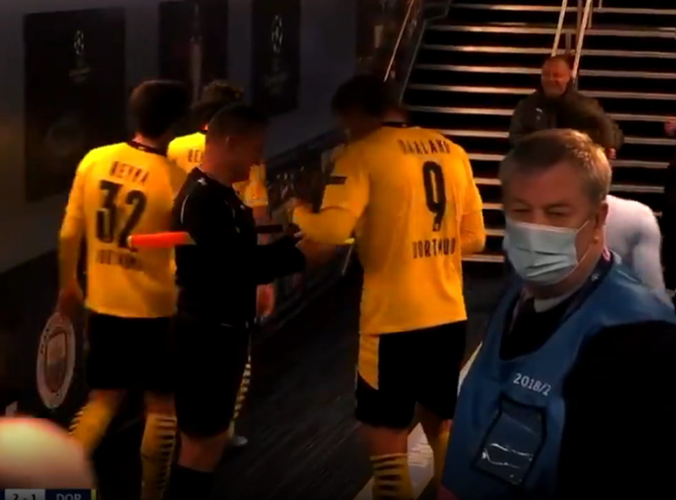 Assistant referee Octavian Sovre asks for Erling Haaland's autograph