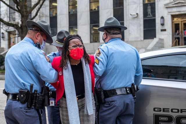 <p>State Rep. Park Cannon, D-Atlanta, is placed into the back of a Georgia State Capitol patrol car after being arrested by Georgia State Troopers at the Georgia State Capitol Building in Atlanta, Thursday, March 25, 2021.</p>
