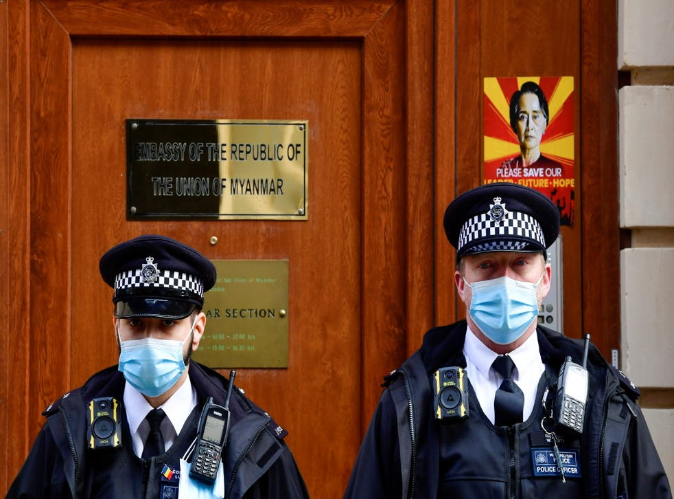 Police officers stand guard outside the Myanmar Embassy in London