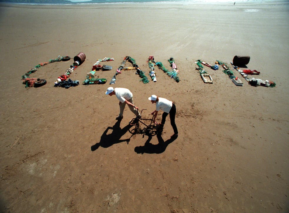 Clean me written on a beach in rubbish (Alamy/PA)