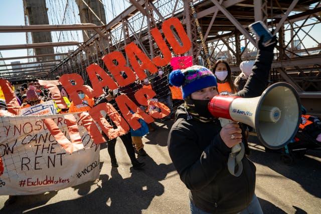 <p>Los manifestantes marchan a través del Puente de Brooklyn para exigir fondos para los trabajadores excluidos en el presupuesto del estado de Nueva York el 5 de marzo de 2021 en la ciudad de Nueva York. La marcha encabezada por trabajadores indocumentados y los recién liberados de la cárcel. Muchos de estos trabajadores excluidos no han podido acceder a beneficios de desempleo, cheques de estímulo y otros programas de asistencia económica destinados a ayudar a las familias trabajadoras afectadas por la pandemia de COVID-19 y la consiguiente crisis económica. </p>