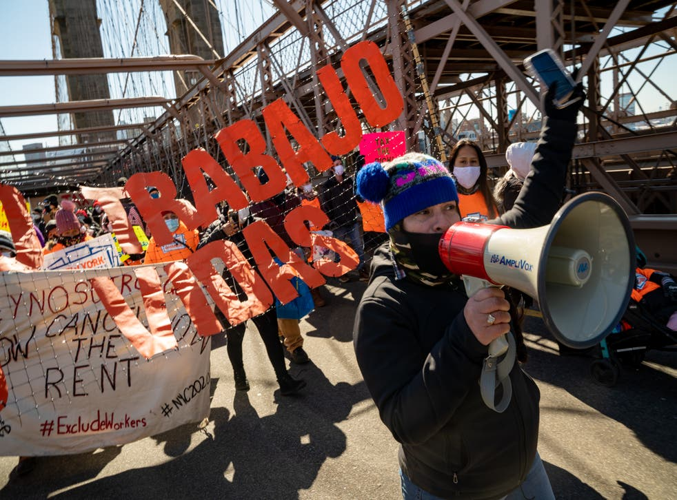 Protestors march across the Brooklyn Bridge to demand funding for excluded workers in the New York State budget on 5 March 2021