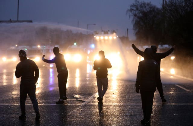 <p>Nationalist youths gesture towards a police line blocking a road near the Peace Wall in Belfast</p>