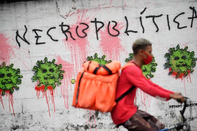 <p>Graffiti showing Jair Bolsonaro's face - the president is under mounting pressure for Brazil's high Covid death toll</p>