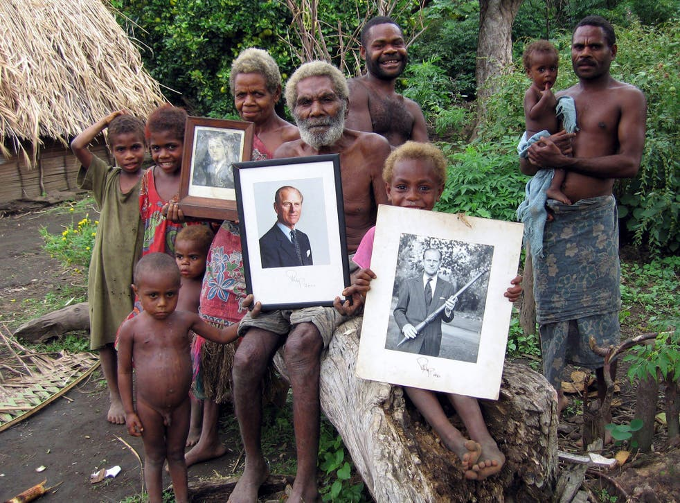 Villagers on the island of Tanna hold up treasured photos of Prince Philip