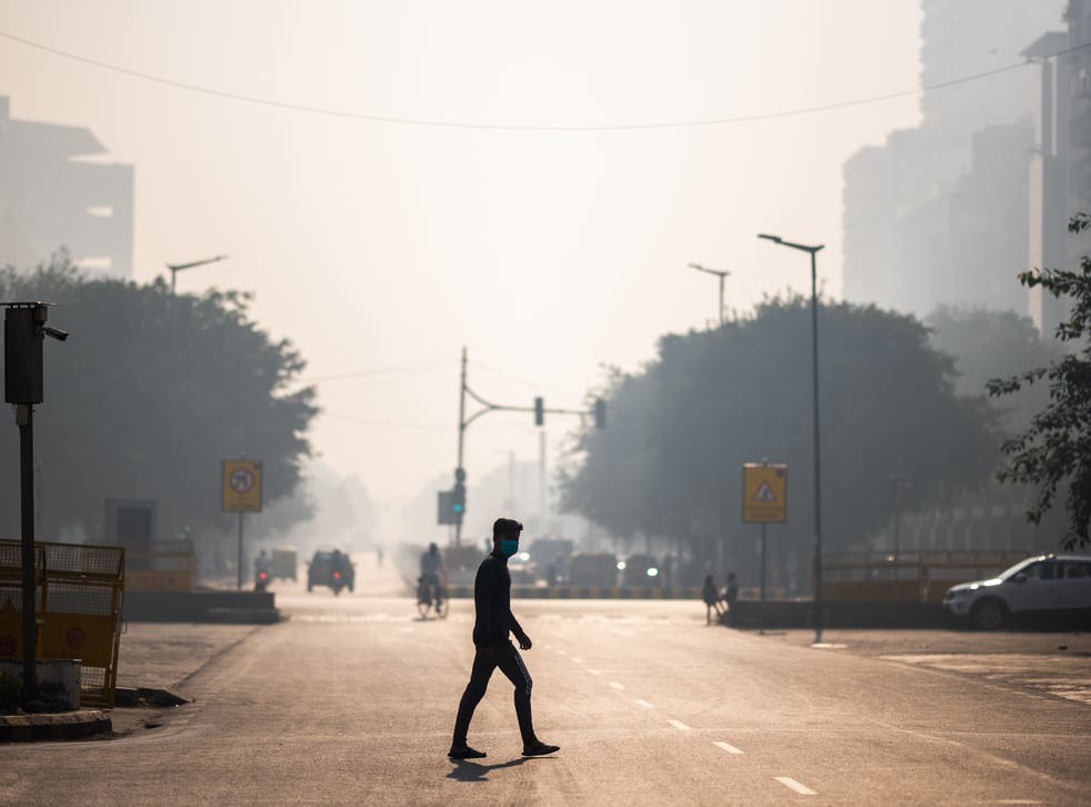 A man wearing a facemask crosses a street amid smoggy condition in New Delhi in October